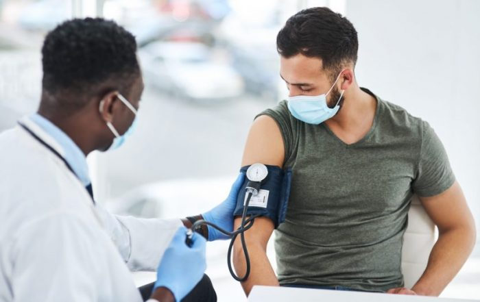 photo of a doctor examining a young man with a blood pressure gauge